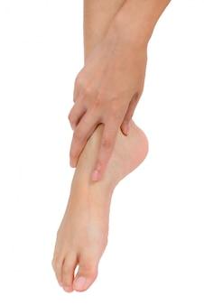 Frauenhand, die ihren fuß hält und den knöchel im schmerzbereich lokalisiert auf weiß massiert