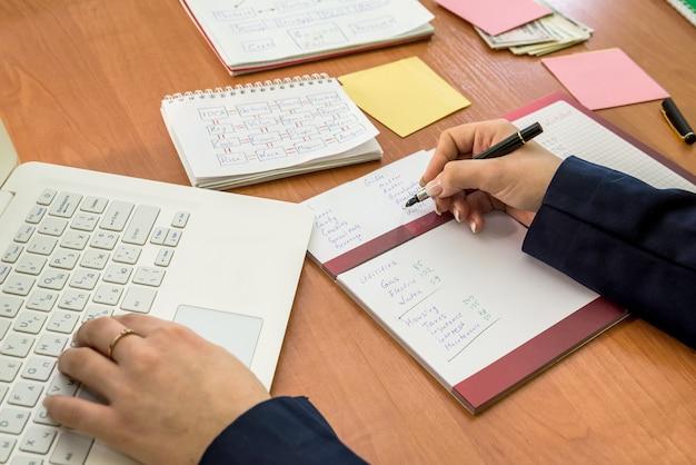 Frauenhand, die im laptop und im monatsbudget arbeitet