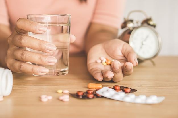 Frauenhand, die in der hand medizin mit glas wasser und uhr auf schreibtisch hält