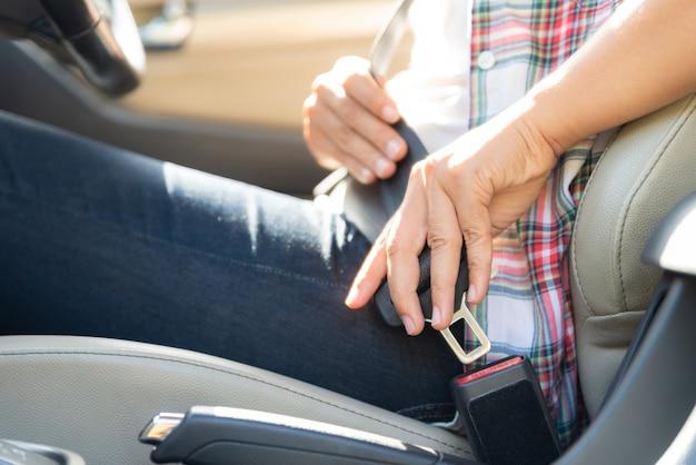 Frauenhand, die innerhalb des autobefestigungssicherheitsgurts sitzt. sicherheitsgurt sicherheit zuerst.