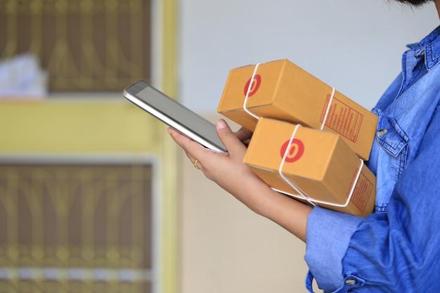 Frauenhand, die intelligentes telefon hält und paket online aufspürt, um status mit hologramm zu aktualisieren