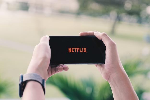Frauenhand, die intelligentes telefon mit netflix-logo hält