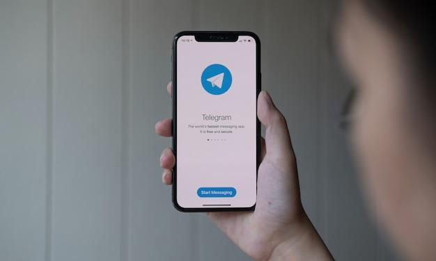 Frauenhand, die iphone x mit sozialem netzwerkdienst hält