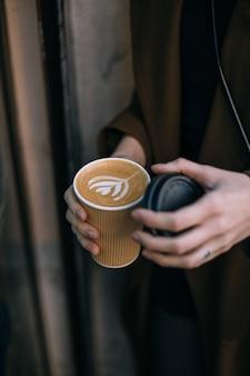 Frauenhand, die kaffee mit latte art auf einem grauen teller von oben erreicht. holztisch im hipster-café. vintage farbfiltereffekt.