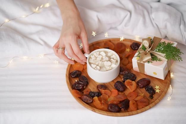 Frauenhand, die kaffee mit marshmallows auf weißen laken mit lichtern nimmt