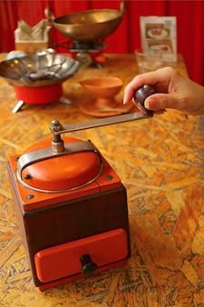 Frauenhand, die kaffeebohnen in einer vibrierenden tragbaren kaffeemühle der vibrierenden farbe für selbst gemachten kaffee reibt