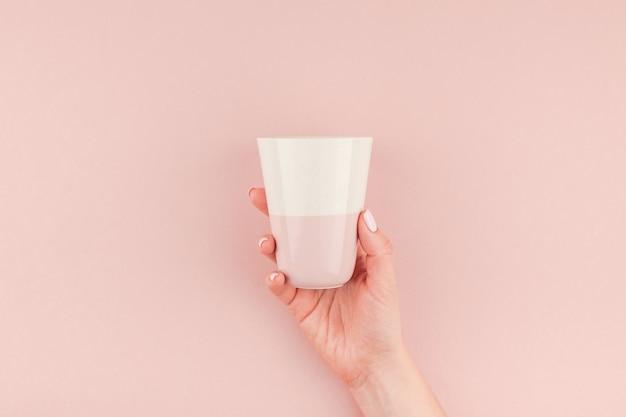 Frauenhand, die kaffeetasse auf rosa hintergrund hält