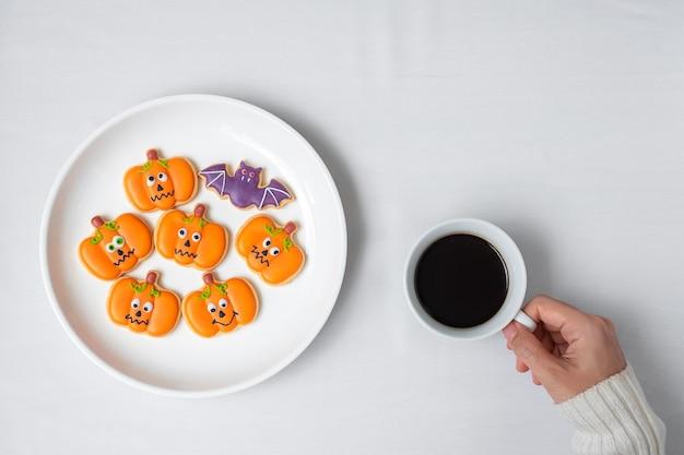 Frauenhand, die kaffeetasse während des essens lustiger halloween-plätzchen hält. fröhlicher halloween-tag, trick oder bedrohung, hallo oktober, herbstherbst, traditions-, party- und urlaubskonzept