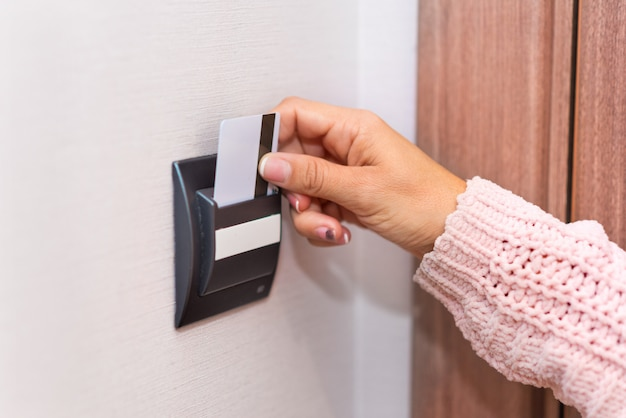 Frauenhand, die karte in das hotelzimmer einfügt