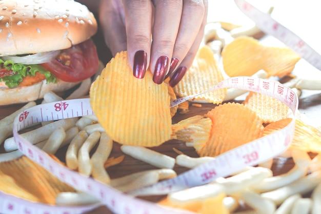 Frauenhand, die kartoffelchips isst ungesundes lebensmittel mit messendem band auf burger, fren hält