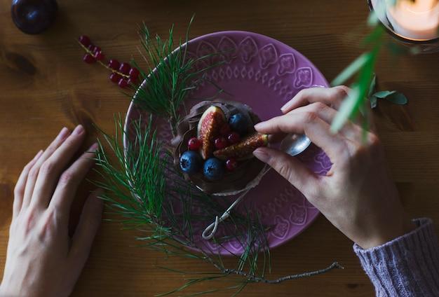 Frauenhand, die kleinen kuchen mit beeren auf weihnachtstabelle hält