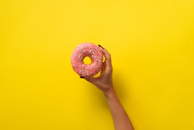 Frauenhand, die köstlichen rosa donut auf gelbem farbhintergrund hält.