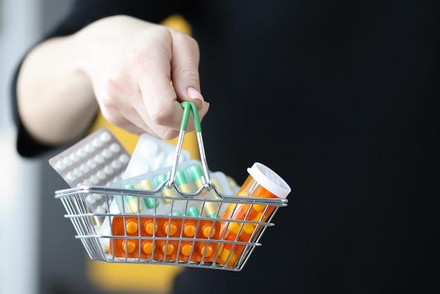 Frauenhand, die korb mit blasen der pillen-nahaufnahme hält. verkauf von medikamenten konzept