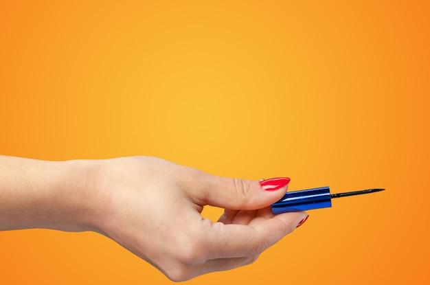 Frauenhand, die kosmetisches werkzeug lokalisiert auf farbhintergrund hält