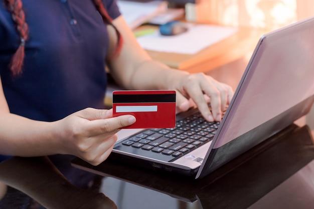 Frauenhand, die kreditkarte hält und laptop-computer verwendet.
