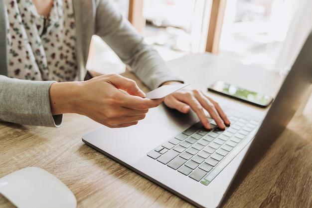 Frauenhand, die kreditkarte hält und laptop für online-einkauf verwendet