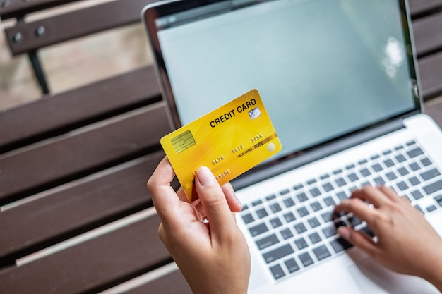 Frauenhand, die kreditkarte hält und laptop, online-einkaufskonzept verwendet