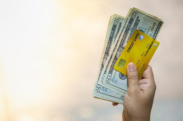 Frauenhand, die kreditkarte und 20 us-dollars banknote mit kopienraum hält.