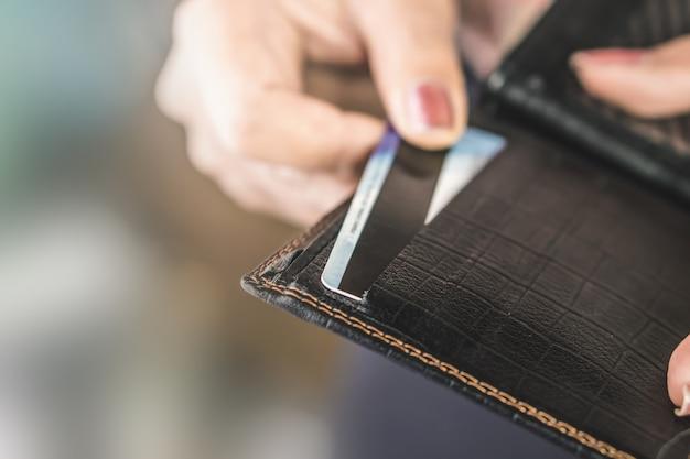 Frauenhand, die kreditkarte vom schwarzen geldbeutel nimmt