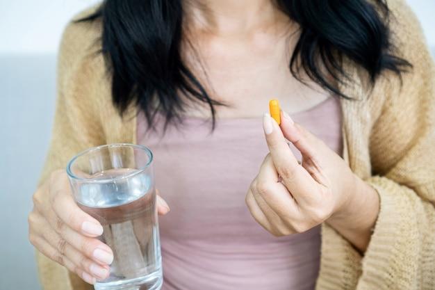 Frauenhand, die kurkuma-pille mit einem glas wasser zur behandlung von saurem reflux nimmt