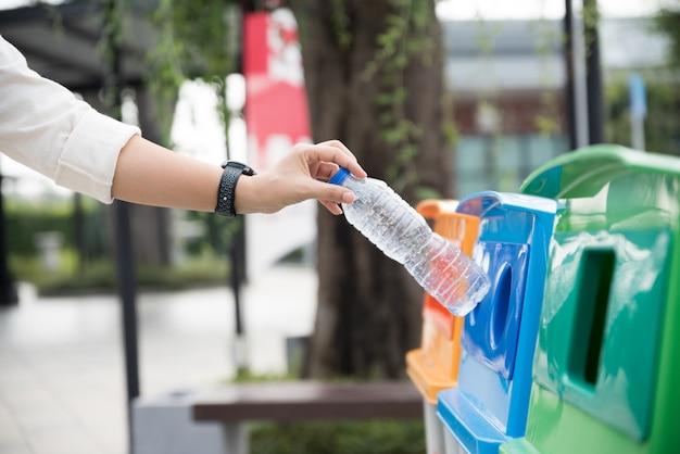 Frauenhand, die leere plastikwasserflasche im wiederverwertungsbehälter wirft.