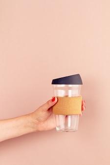 Frauenhand, die leere trommel, wiederverwendbare kaffeetasse hält. plastikfreies und abfallfreies lifestyle-konzept