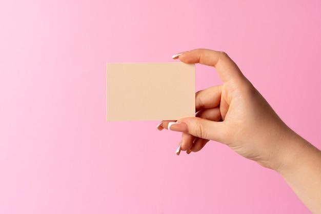 Frauenhand, die leere visitenkarte auf rosa hintergrund zeigt.