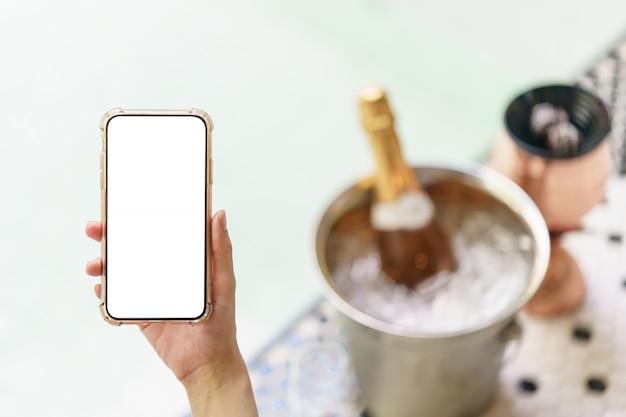 Frauenhand, die leeres weißes bildschirmhandy mit champagnerflasche im eiskübel und zwei gläsern nahe whirlpool-pool hält.