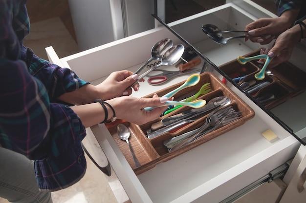 Frauenhand, die löffel in der küche hält.