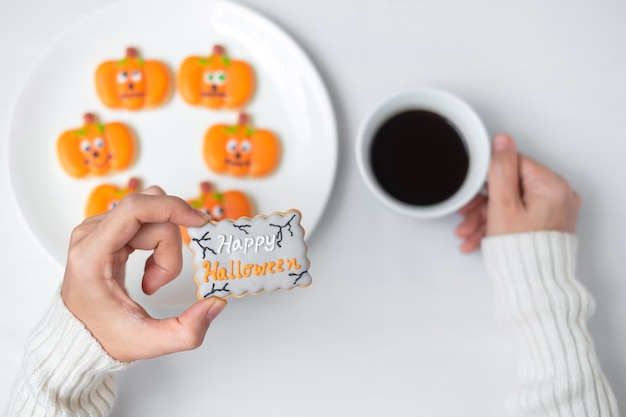 Frauenhand, die lustiges halloween-plätzchen während des kaffeetrinkens hält. fröhlicher halloween-tag, trick oder bedrohung, hallo oktober, herbstherbst, traditions-, party- und urlaubskonzept