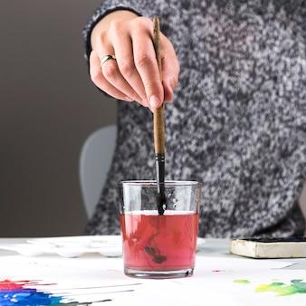 Frauenhand, die malerpinsel im glas für das säubern hält