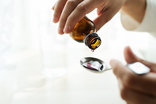 Frauenhand, die medikation oder hustensirup von flasche zu löffel gießt. gesundheitskonzept