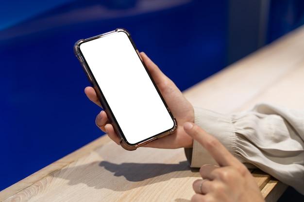 Frauenhand, die mobiles modell des weißen bildschirms zeigt