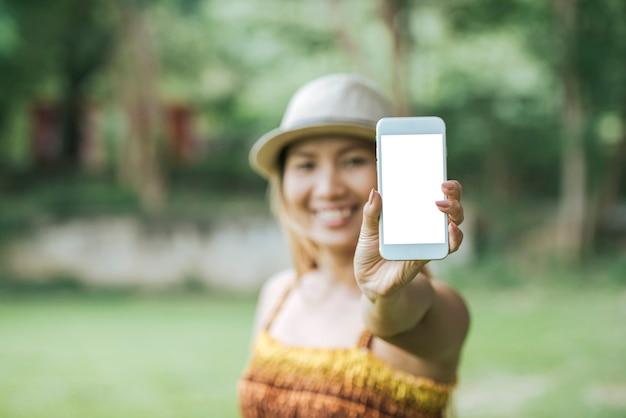 Frauenhand, die mobiltelefon, smartphone mit weißem schirm hält