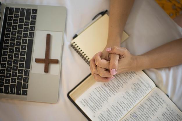 Frauenhand, die morgens auf heiliger bibel betet studieren sie die bibel mit online-gottesdienst.