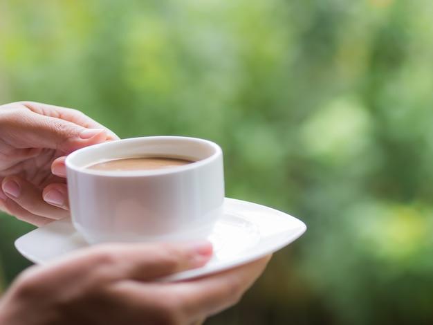 Frauenhand, die morgens einen tasse kaffee am garten hält