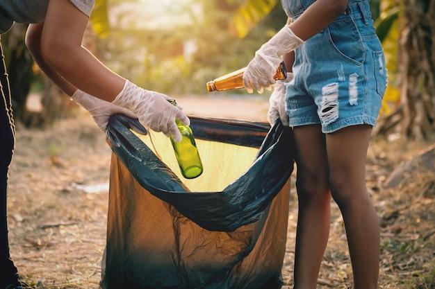 Frauenhand, die müllglasflasche für das säubern am park aufhebt