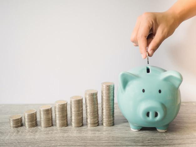 Frauenhand, die münze in blaues sparschwein mit münzstapel-wachstumsdiagramm steckt, geld für zukünftige investitionspläne und pensionsfondskonzept sparend