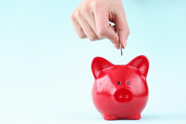 Frauenhand, die münze in rotes sparschwein wirft. geld sparen konzept