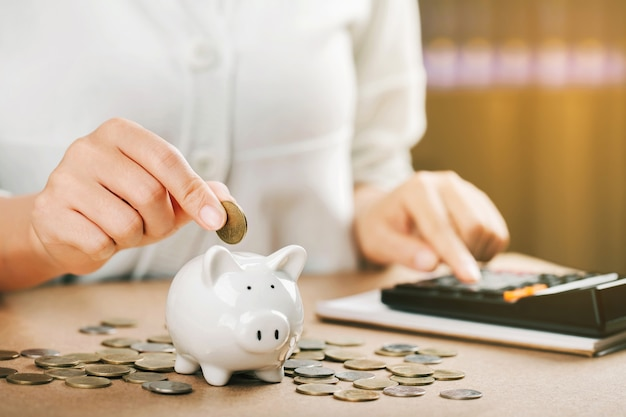 Frauenhand, die münzen hält, die in sparschwein setzen. konzept geld sparen für die finanzbuchhaltung