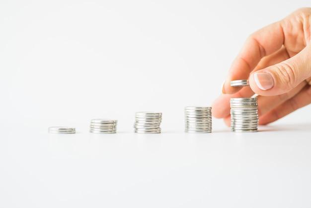 Frauenhand, die münzen zum stapel hinzufügt