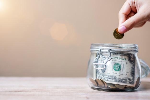 Frauenhand, die münzengeld in glasgefäß einsetzt. weltspartag, geschäft