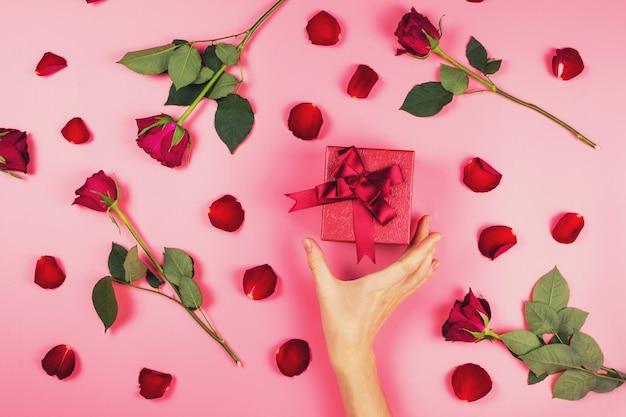 Frauenhand, die nach einem geschenk in der roten schachtel auf rosa hintergrund greift, bedeckt mit roten rosen und blütenblättern, romantische flache lage