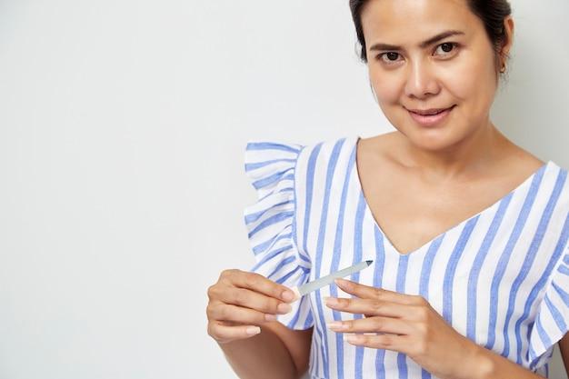 Frauenhand, die nägel mit nagelfeile raspelt