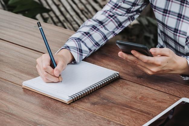 Frauenhand, die notizblock schreibt und telefon auf holztisch am kaffeehaus hält