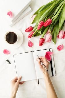 Frauenhand, die notizen im geöffneten notizbuch macht, verziert mit tulpen, kaffeetasse und büchern, draufsicht flach lag