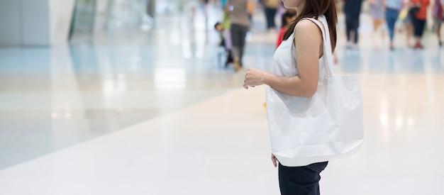 Frauenhand, die öko-einkaufstasche im speicher mit kopierraum für text hält. umweltschutz, null abfall, wiederverwendbar, sag nein plastik, weltumwelttag und tag der erde konzept