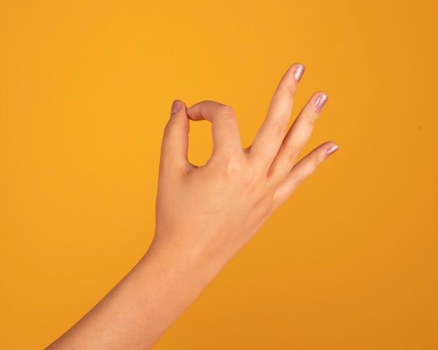 Frauenhand, die ok geste macht, auf gelbem raum