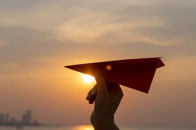 Frauenhand, die orange papierrakete mit während des sonnenuntergangs hält