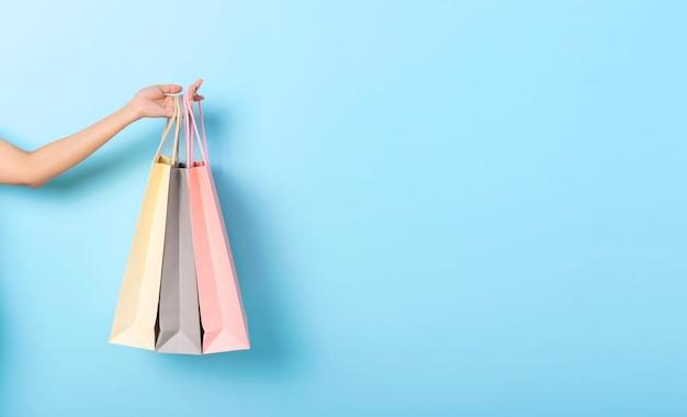 Frauenhand, die papiereinkaufstasche auf blauem fahnenhintergrund hält. rabatte und verkaufskonzept. panoramabild